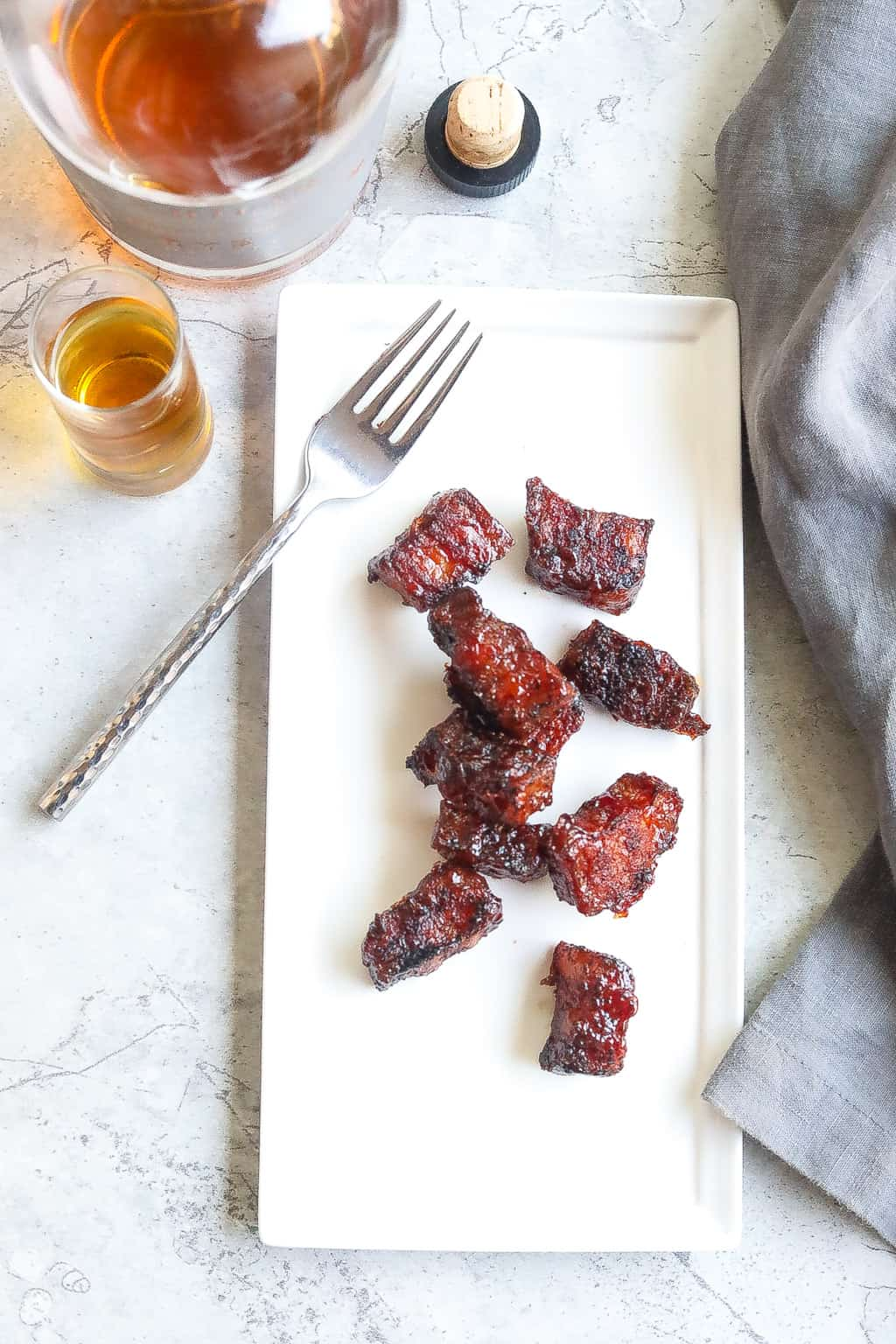 smoked pork belly burnt ends on a white plate