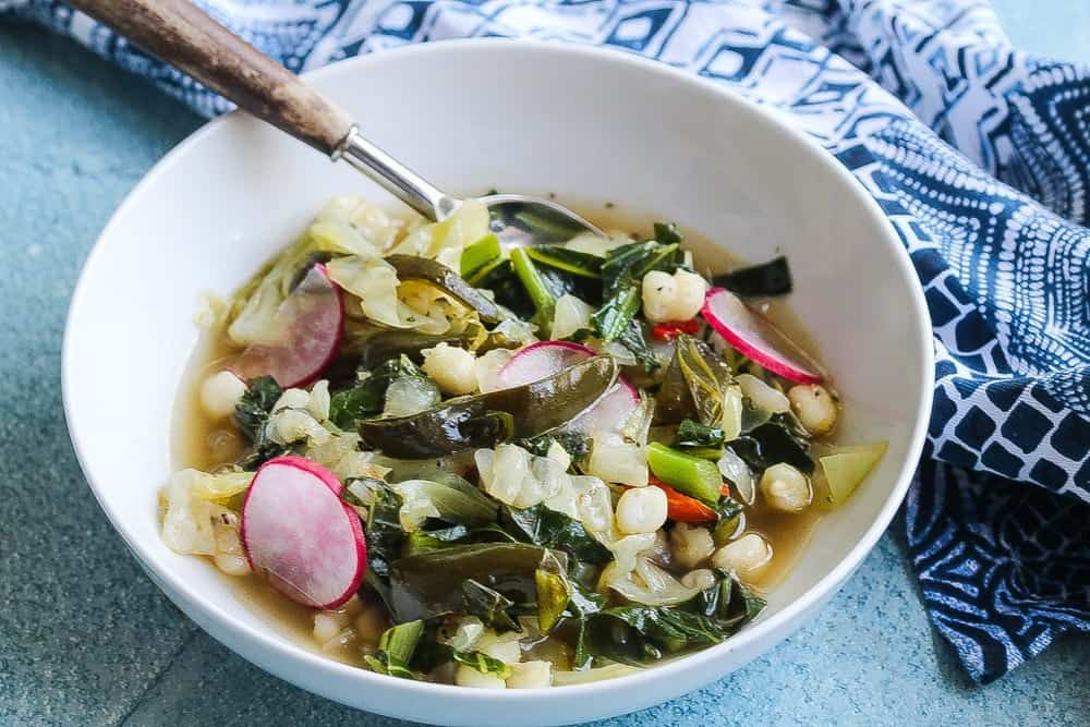 vegan cabbage poblano pozole with collard greens in a bowl
