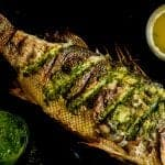 whole baked fish recipe on black tray
