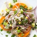 peruvian ceviche on a white plate with sweet potatoes and corn