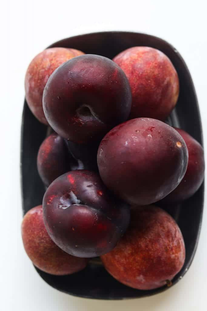 dark plums piled on a plate