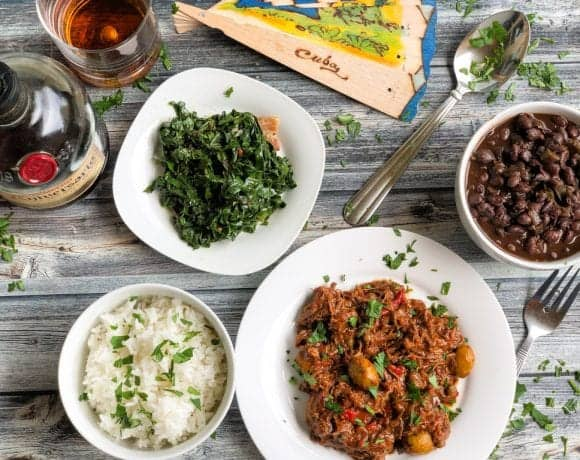 tray with cuban ropa vieja, black beans, rice, greens, and rum