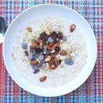 overnight oatmeal with fonio topped with trail mix in a white bowl