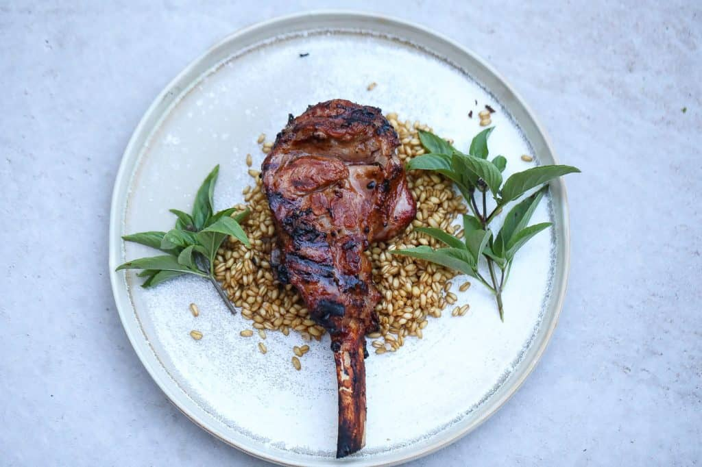 grilled veal chops on a white plate with grains
