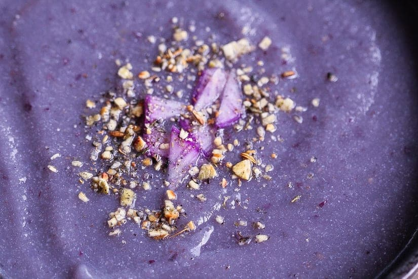 purple soup with purple cauliflower & purple potatoes in black bowl topped with spices