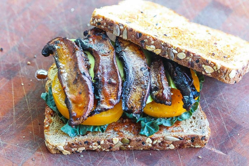 Vegan BLT Sandwich with mushroom slices with yellow tomatoes and black kale on two slices of bread