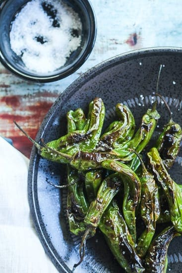 pan-fried padron peppers on a black plate