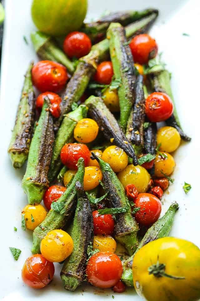 skillet blistered okra and tomatoes on a white platter
