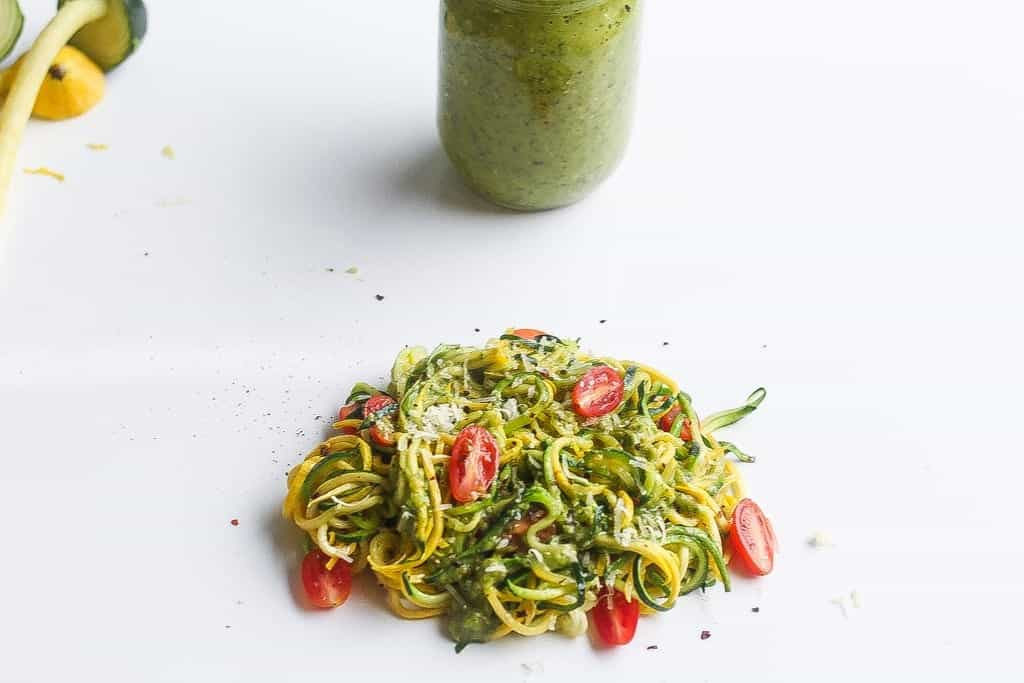 zucchini pasta with collard green salsa verde with cherry tomatoes.
