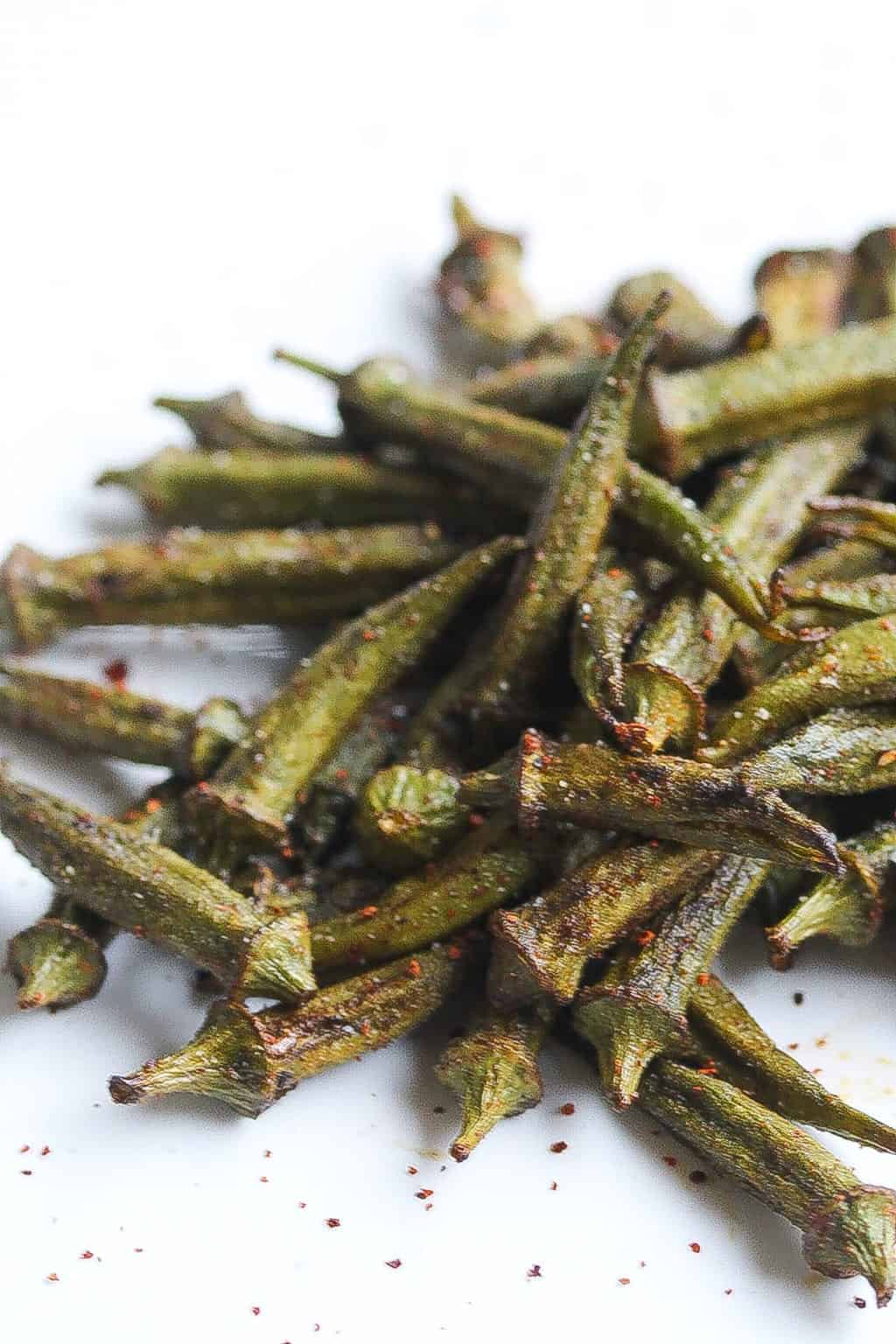 roasted okra pods on a white plate