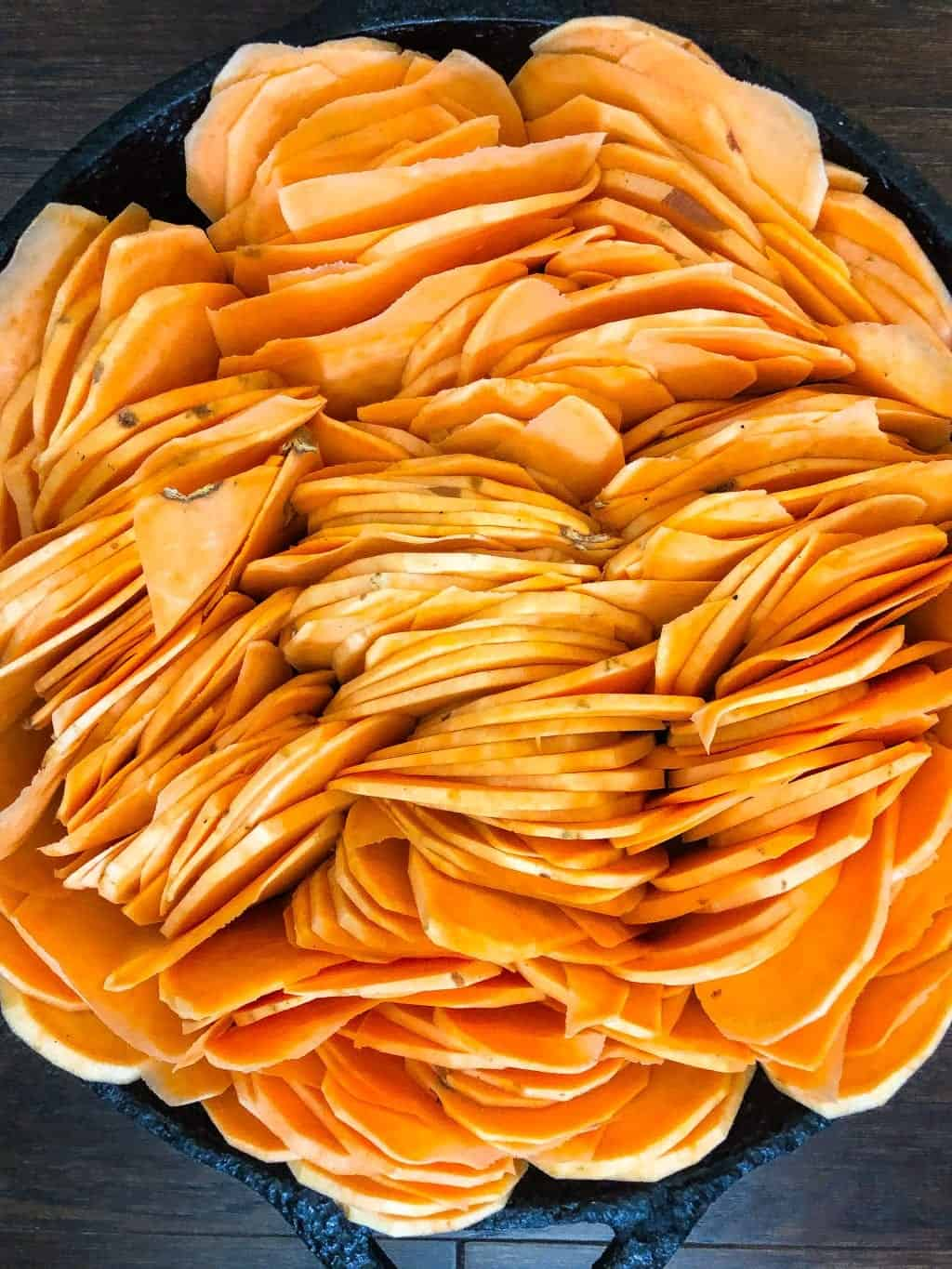 slices of raw sweet potatoes in a skillet