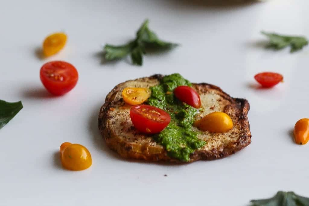Roasted celery root steak on a plated topped with cherry tomatoes and collard greens salsa verde