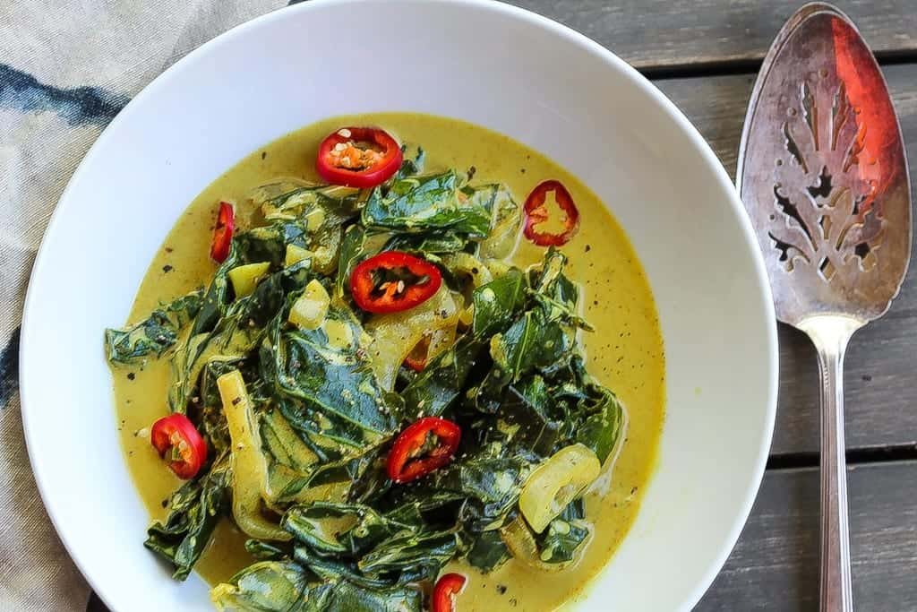 coconut curry braised vegetarian collard greens in a white bowl topped with red chilis