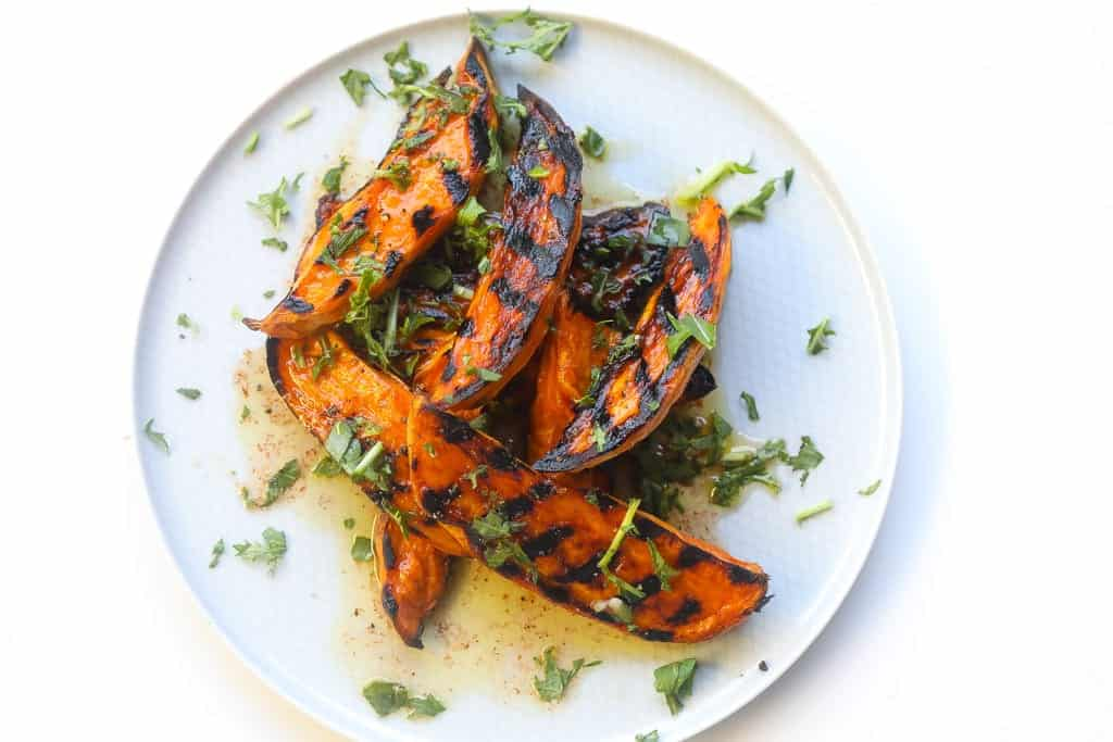 grilled sweet potato wedges on a plate topped with chili lime sauce