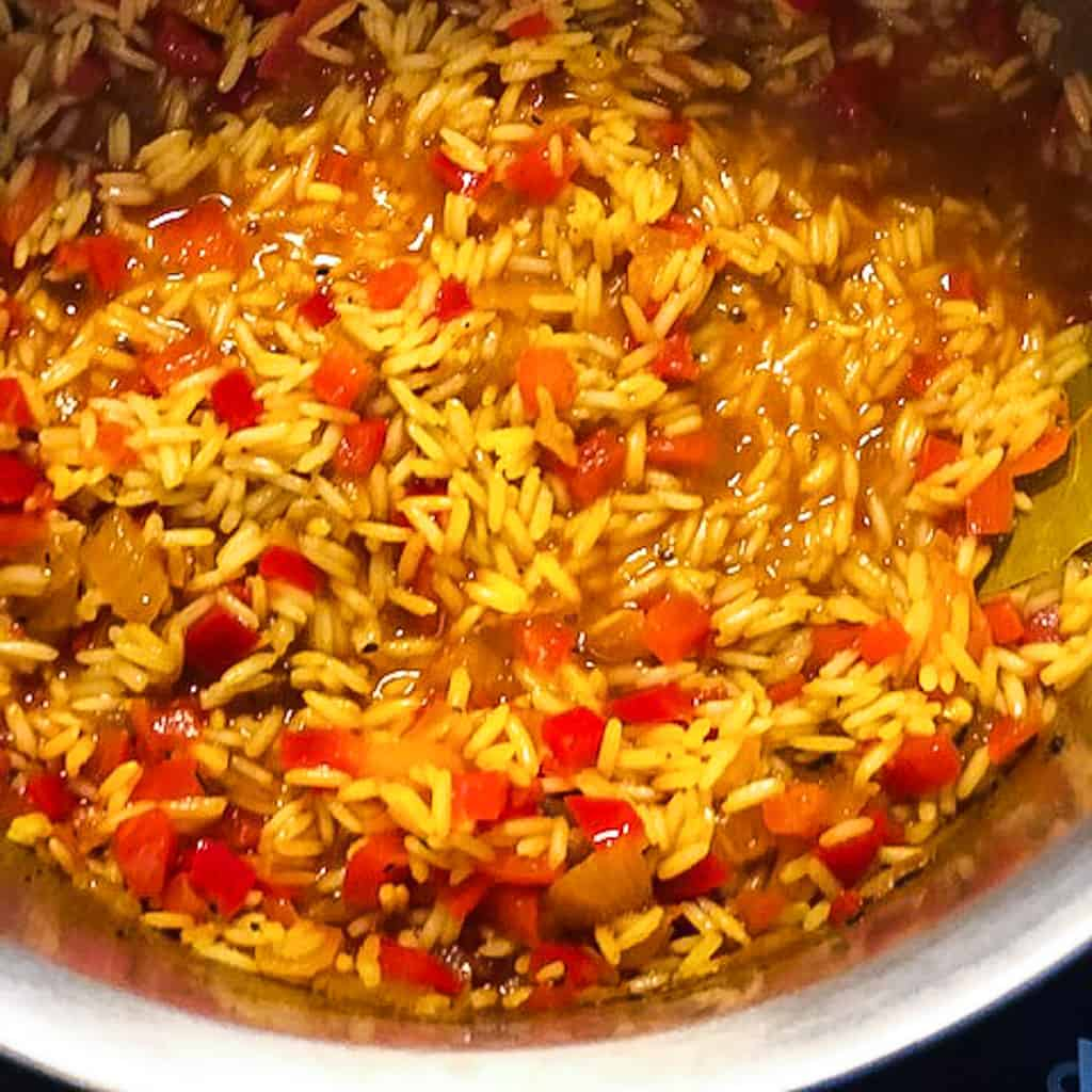 jollof rice with red bell peppers in pot