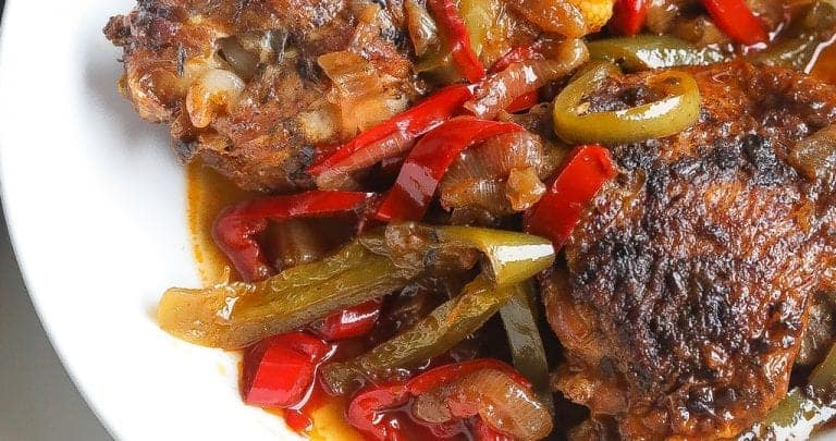 Brown stew chicken topped with peppers in a white bowl