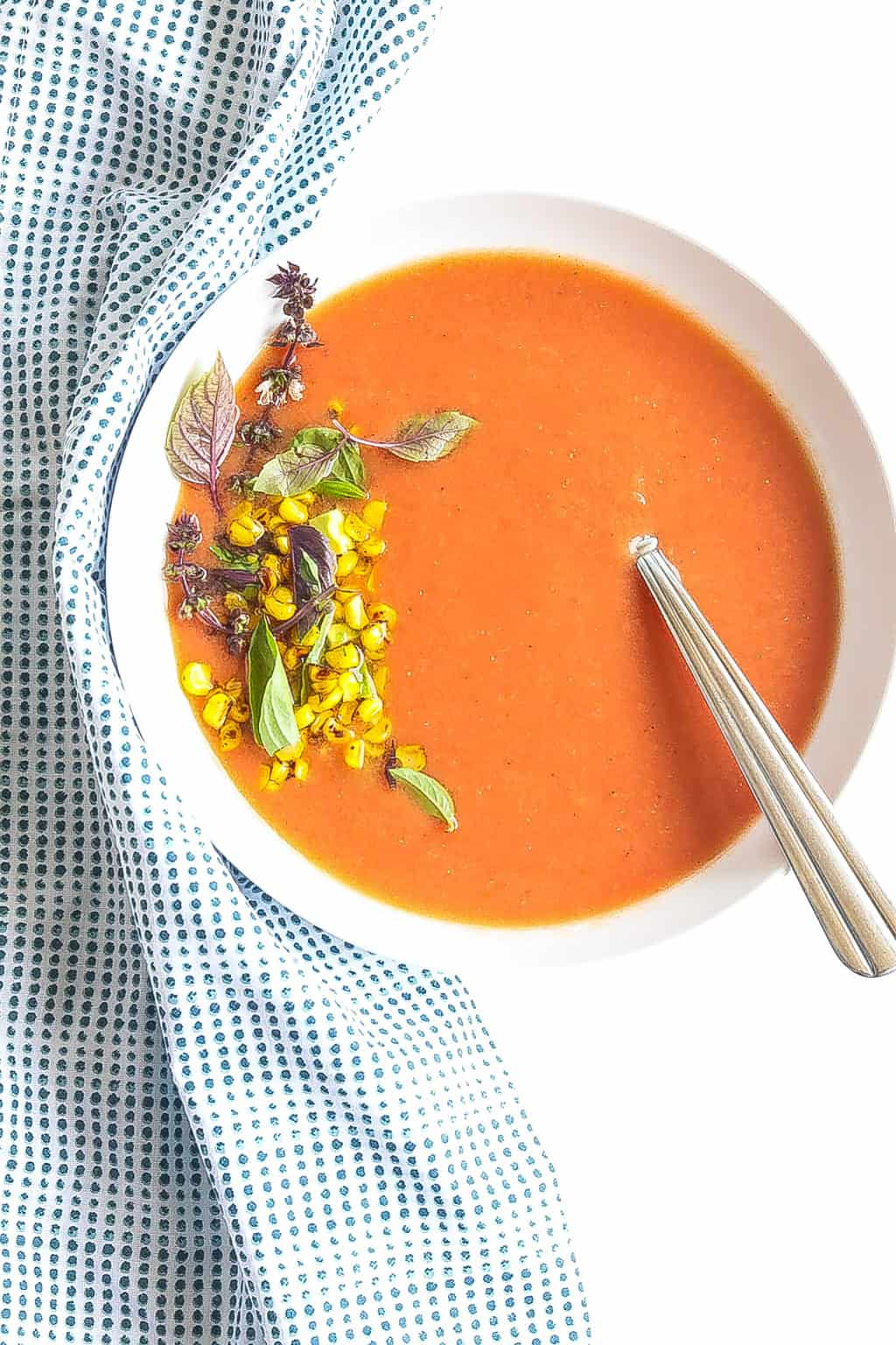 chilled peach gazpacho soup in a bowl topped with corn and avocado