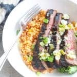 grilled flank steak bowl with couscous and greens