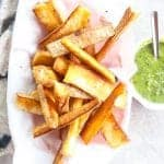 yuca fries with green dipping sauce on a platter