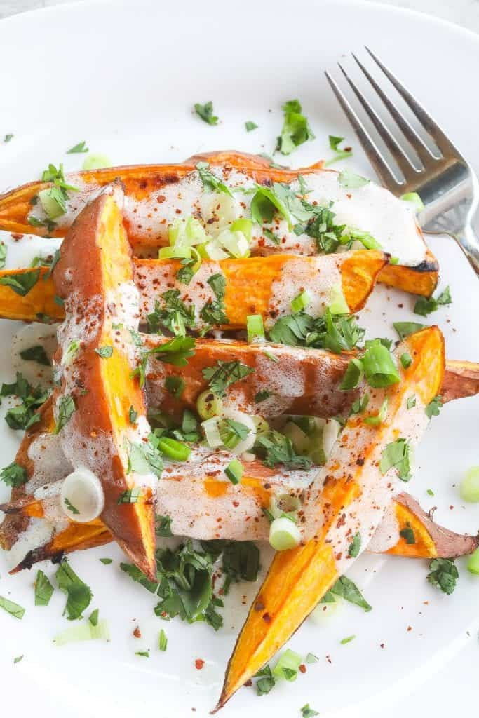 roasted sweet potatoes (wedges) topped with yogurt sauce and green onions on a white plate