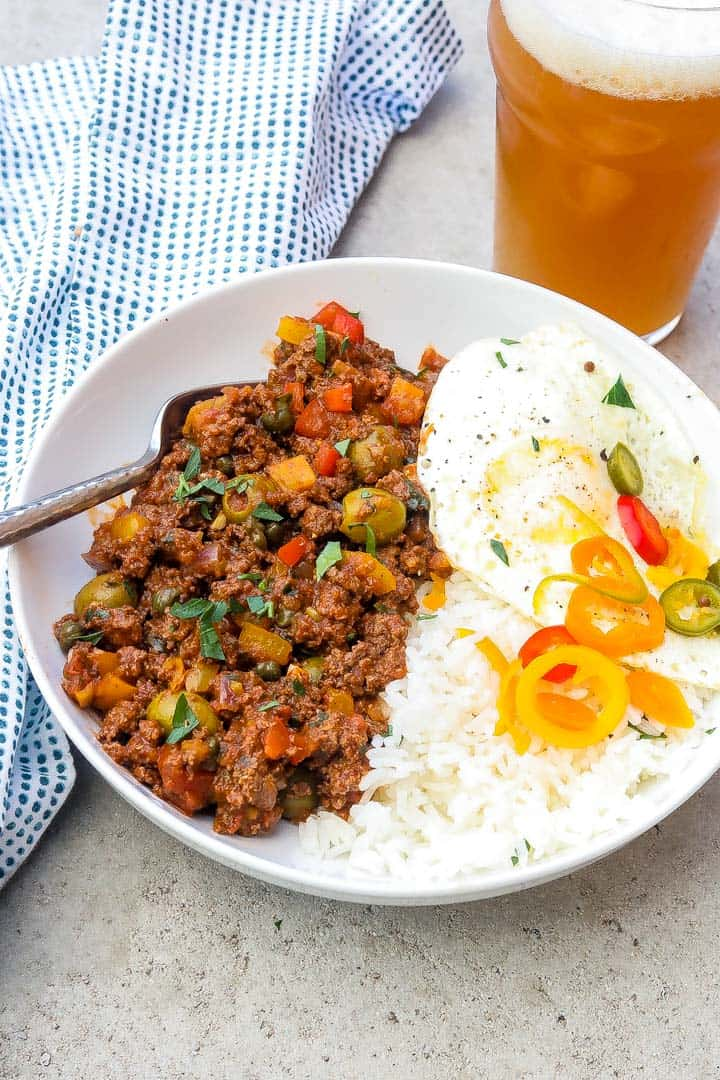 cuban picadillo in a white bowl with rice, fried eggs, and peppers.