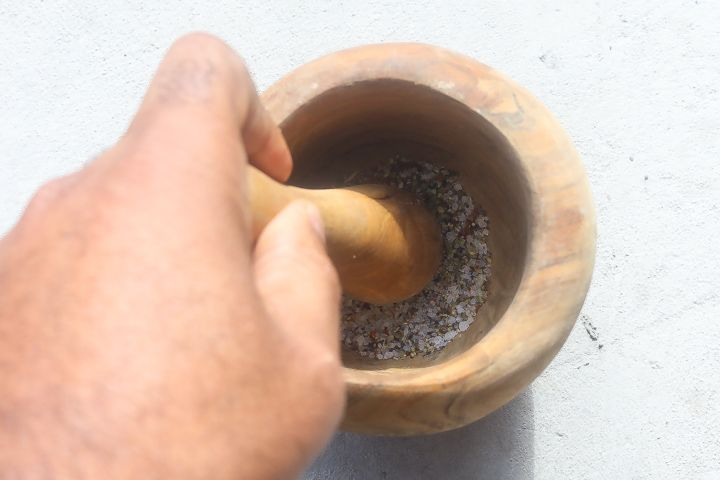 spices in a mortar being grinded with a pestle
