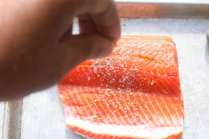 sprinkling spices on a raw fish