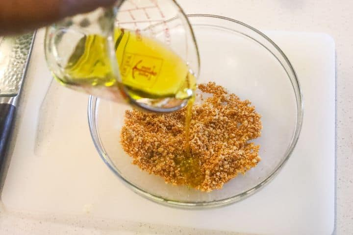 oil being added to bowl of spices