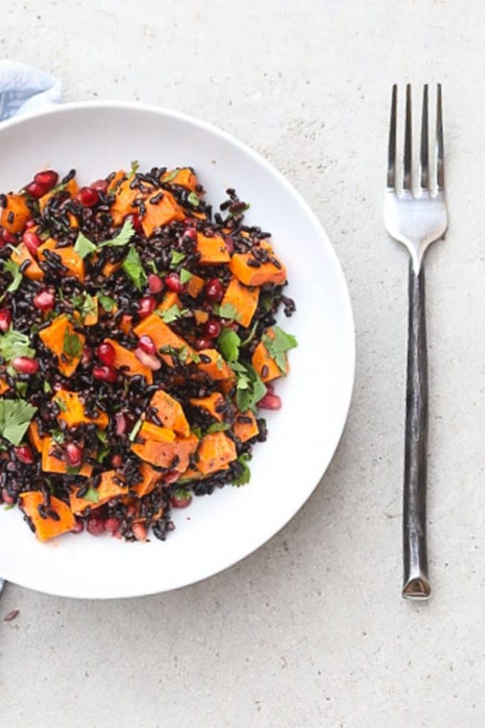 black rice salad with sweet potatoes and pomegranate seeds in a bowl