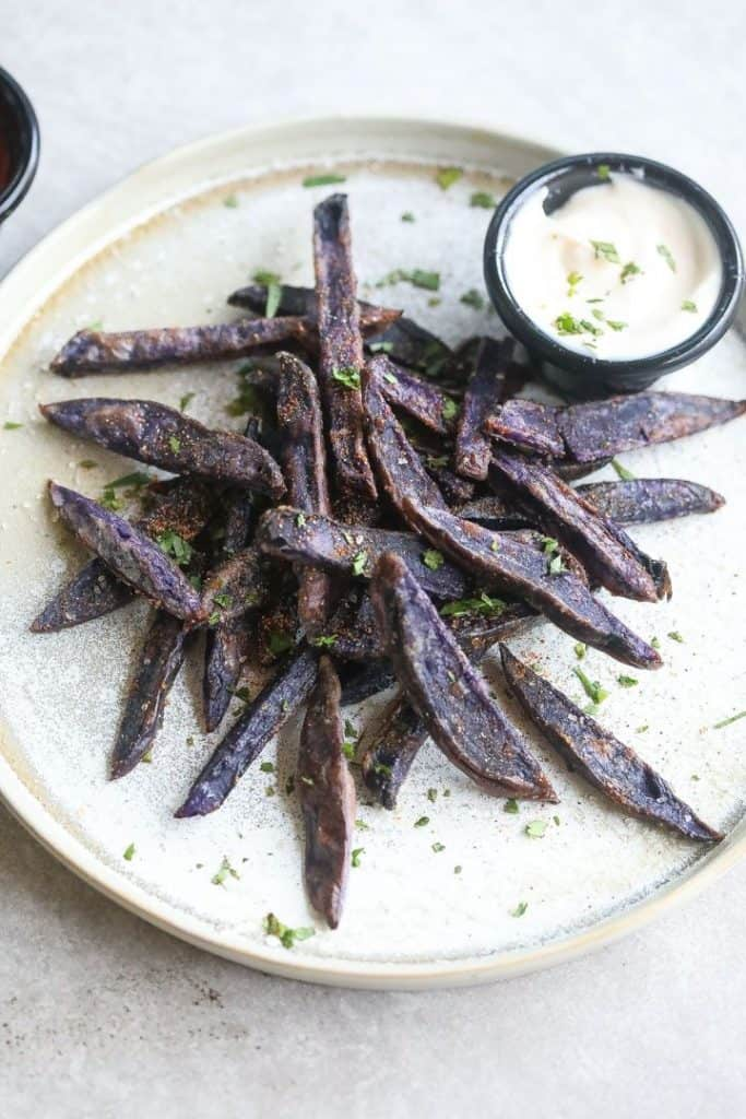 purple potato fries on a plate with mayonnaise