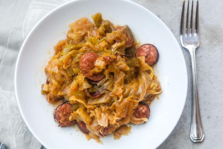 cabbage and sausage on a white plate