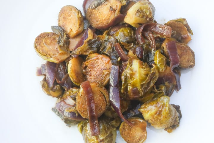 braised brussel sprouts with onions on white plate