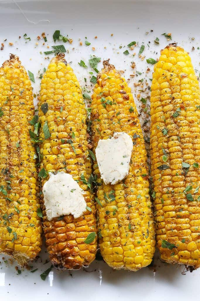 corn on the cob topped with fresh herbs and compound butter