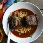 beef short ribs in white bowl with sauce
