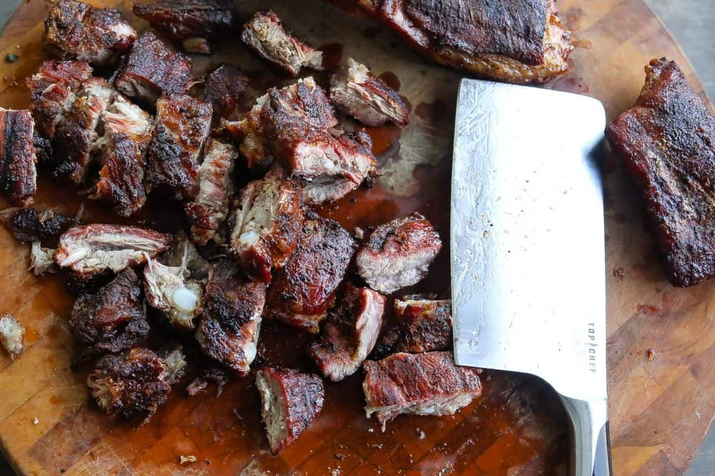 chopped ribs on wood block with meat cleaver