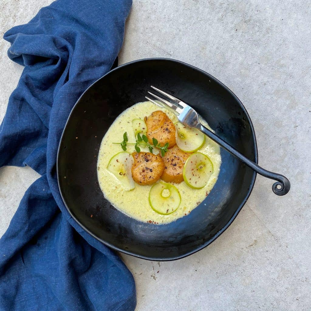smoked scallops in black bowl with sauce