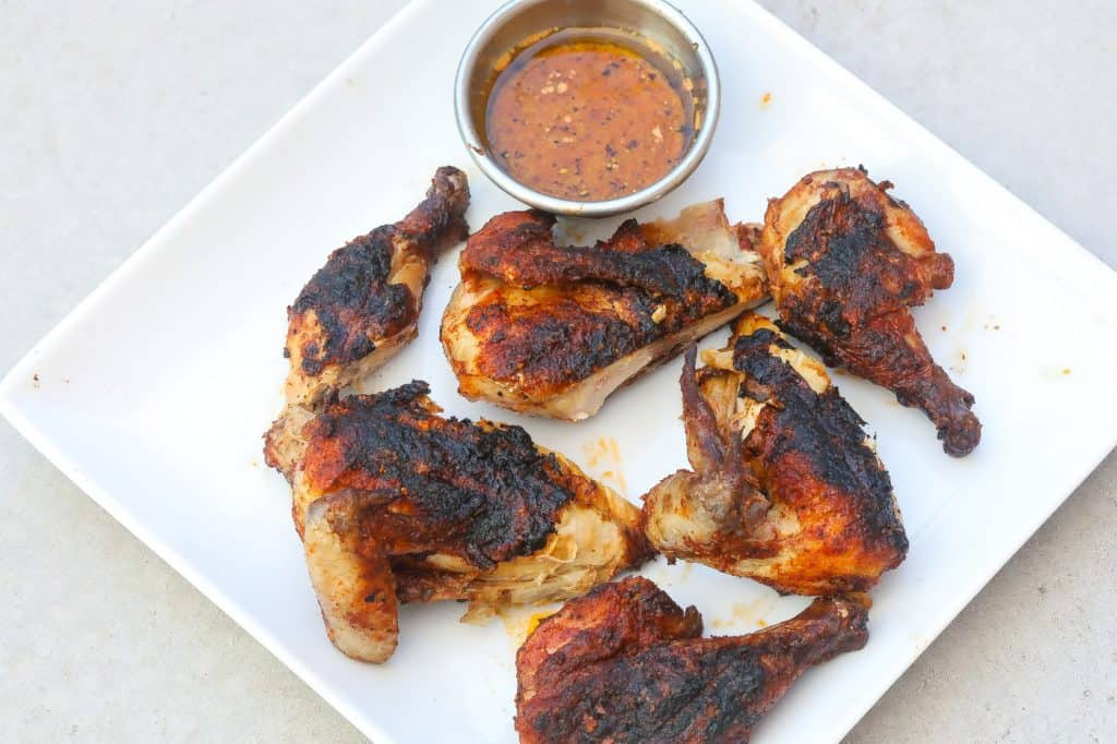 grilled chicken pieces on a white plate
