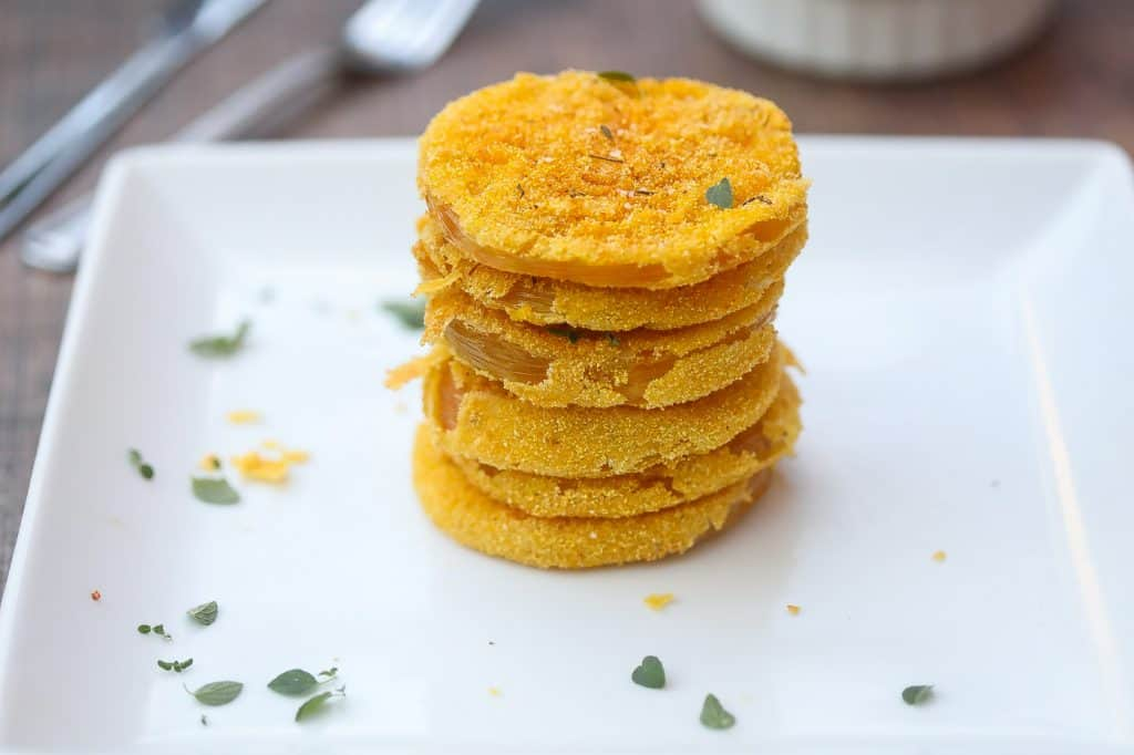 fried green tomatoes stacked on a white plate