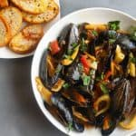 mussels in a bowl with a side of toast