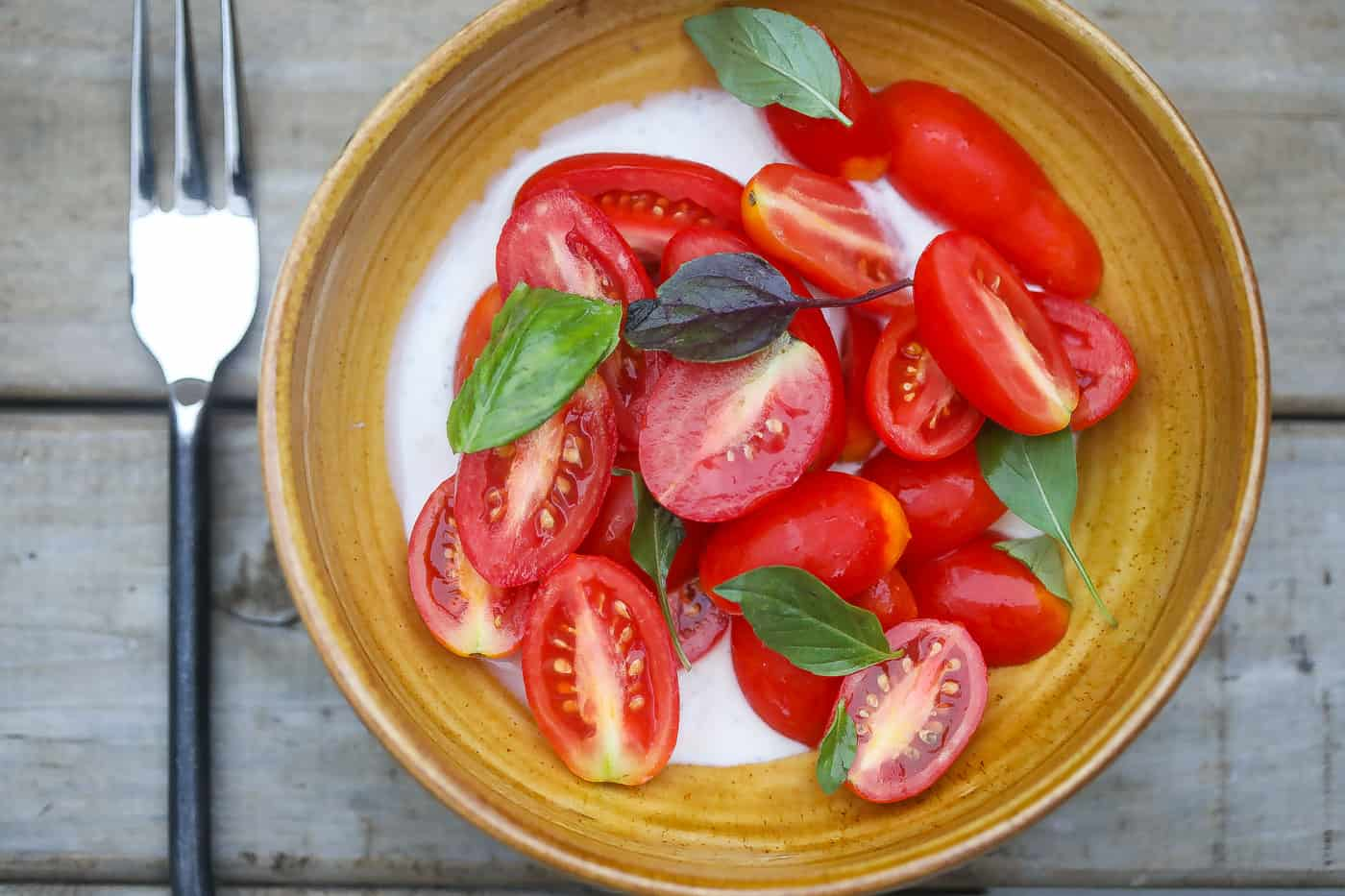 tomatoes and basil in a yellow bowl