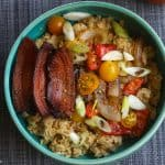 oatmeal topped with bacon and vegetables in a blue bowl