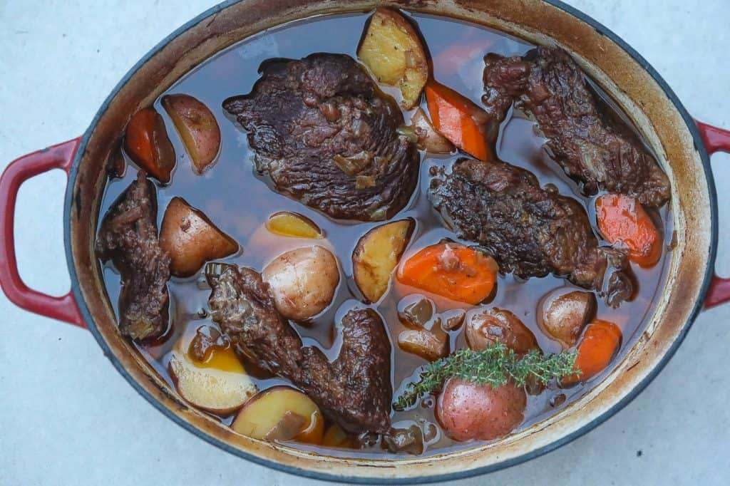 beef pot roast in a dutch oven with carrots and potatoes