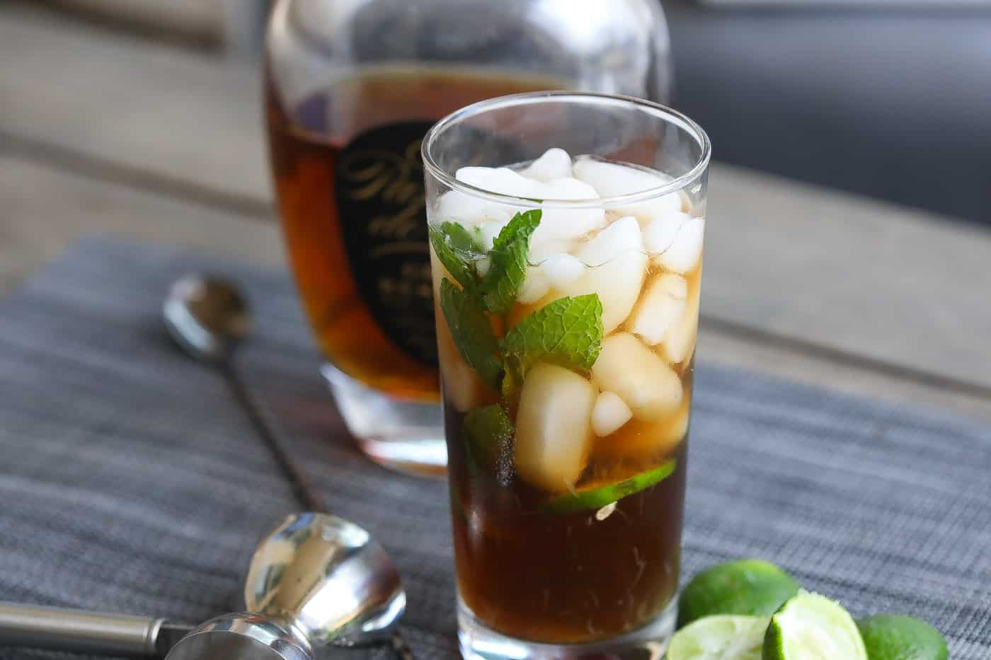 cuba libre cocktail in a tall glass with mint