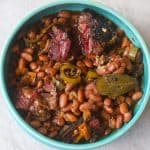 pinto beans with brisket in a blue bowl