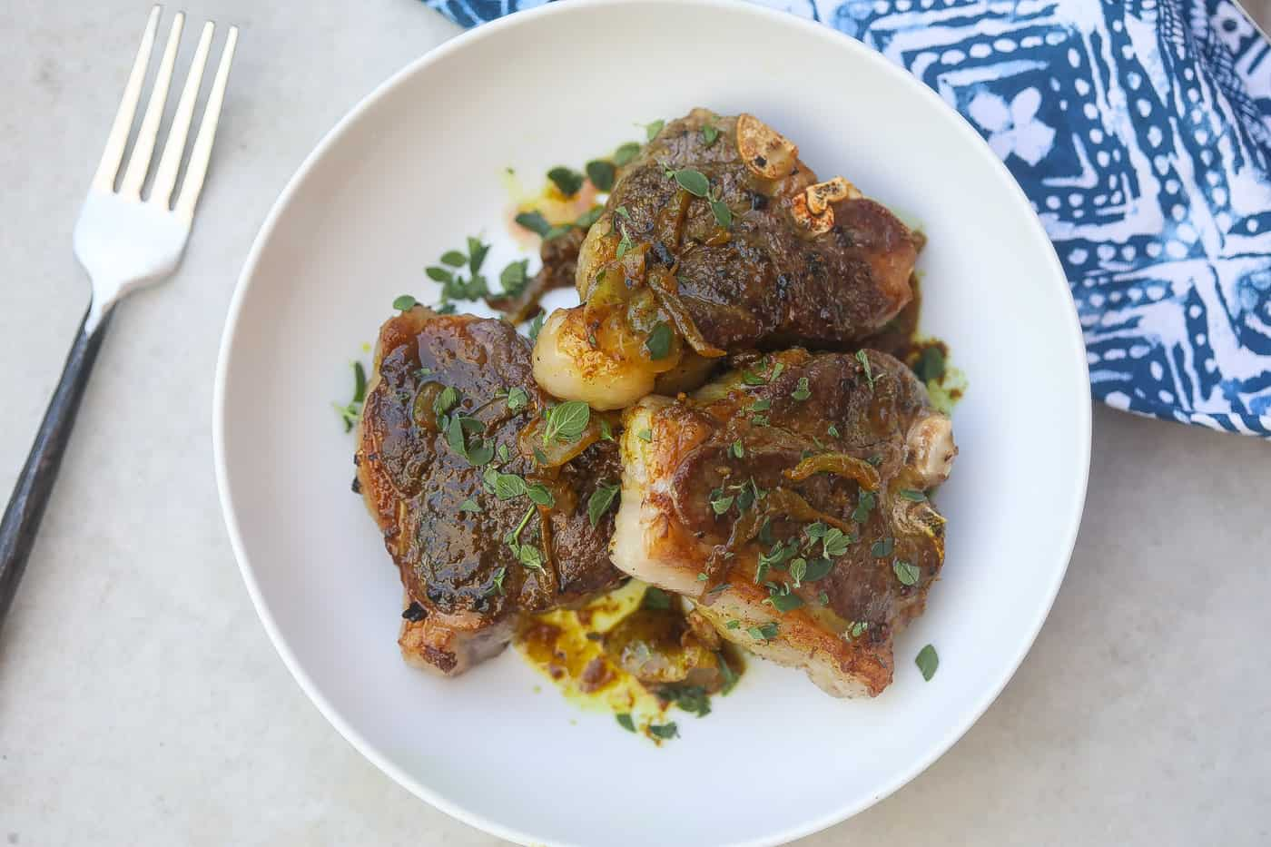 lamb chops on a white plate with spinach and grains