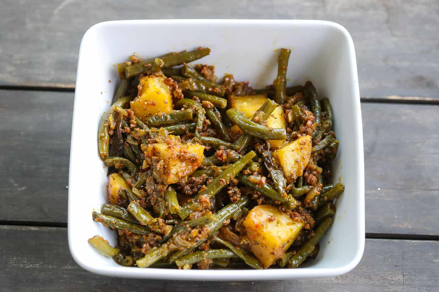 green beans and potatoes in white square bowl