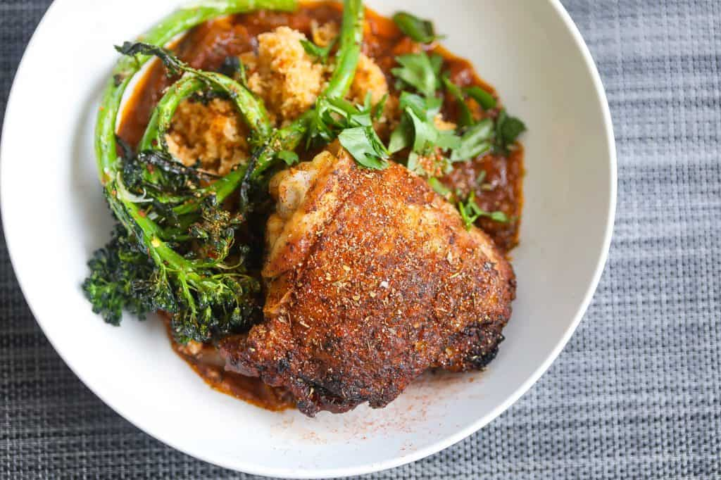 crispy chicken thighs with broccoli and fonio grain in white bowl