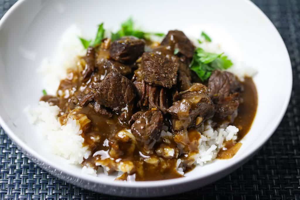 beef tips and rice topped with gravy in a white bowl