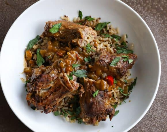 smothered turkey necks on top of a bowl of rice
